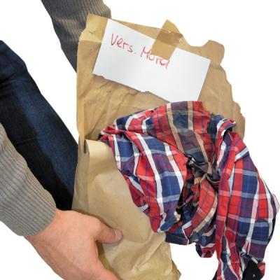 """""""Versuchter Mord""""– ein Zettel an einem karierten Hemd, das eindeutig einen großen Blutfleck aufweist, gibt einen ersten Hinweis."""